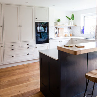 This is an example of a medium sized contemporary u-shaped kitchen in Other with a double-bowl sink, shaker cabinets, beige cabinets, white splashback, ceramic splashback, stainless steel appliances, light hardwood flooring, a breakfast bar, brown floors and white worktops.
