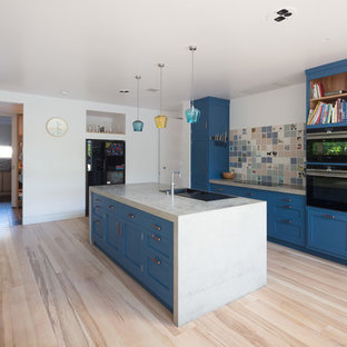 Inspiration for a large modern galley open plan kitchen in Hertfordshire with a drop-in sink, flat-panel cabinets, blue cabinets, solid surface benchtops, multi-coloured splashback, ceramic splashback, black appliances, light hardwood floors, with island and green benchtop.