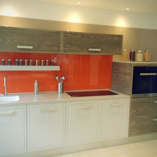 Small modern kitchen photos - Small minimalist single-wall kitchen photo in London with an integrated sink, flat-panel cabinets, light wood cabinets, solid surface countertops, orange backsplash, glass sheet backsplash, stainless steel appliances and no island