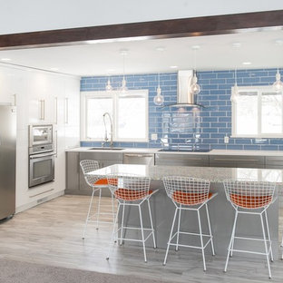 This is an example of a mid-sized beach style l-shaped kitchen in Other with a single-bowl sink, recycled glass benchtops, blue splashback, glass tile splashback, stainless steel appliances, ceramic floors, with island, flat-panel cabinets and grey cabinets.