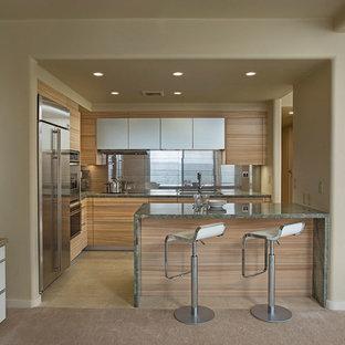 ハワイのコンテンポラリースタイルのおしゃれなキッチン (シングルシンク、フラットパネル扉のキャビネット、中間色木目調キャビネット、御影石カウンター、メタリックのキッチンパネル、磁器タイルのキッチンパネル、シルバーの調理設備の、磁器タイルの床、緑のキッチンカウンター) の写真