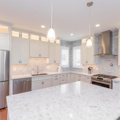 Inspiration for a mid-sized timeless l-shaped medium tone wood floor and brown floor eat-in kitchen remodel in DC Metro with an undermount sink, recessed-panel cabinets, white cabinets, marble countertops, gray backsplash, marble backsplash, stainless steel appliances and an island