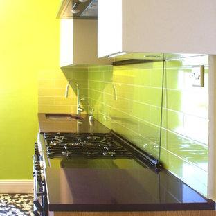 ロンドンの小さいコンテンポラリースタイルのおしゃれなキッチン (シングルシンク、フラットパネル扉のキャビネット、中間色木目調キャビネット、珪岩カウンター、緑のキッチンパネル、サブウェイタイルのキッチンパネル、黒い調理設備、アイランドなし) の写真