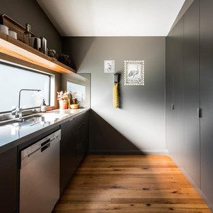 Immagine di una cucina parallela minimal chiusa con lavello da incasso, ante lisce, ante nere, paraspruzzi a finestra, elettrodomestici in acciaio inossidabile, pavimento in legno massello medio, nessuna isola, pavimento marrone e top grigio