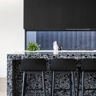 Contemporary kitchen in Melbourne with flat-panel cabinets, black cabinets, window splashback, light hardwood floors, with island, beige floor and multi-coloured benchtop.