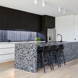 Ispirazione per una grande cucina contemporanea con lavello a doppia vasca, ante lisce, ante nere, top alla veneziana, paraspruzzi a finestra, elettrodomestici in acciaio inossidabile, parquet chiaro, isola e top bianco
