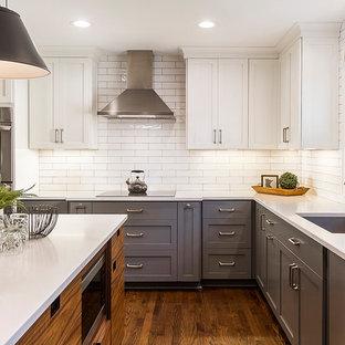 Mittelgroße Klassische Wohnküche in L-Form mit Unterbauwaschbecken, Schrankfronten im Shaker-Stil, grauen Schränken, Quarzit-Arbeitsplatte, Küchenrückwand in Weiß, Rückwand aus Metrofliesen, Küchengeräten aus Edelstahl, braunem Holzboden, Kücheninsel, braunem Boden und weißer Arbeitsplatte in Minneapolis