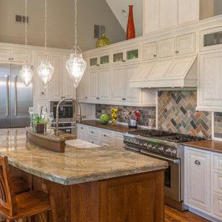 Offene, Mittelgroße Landhaus Küche in L-Form mit Landhausspüle, profilierten Schrankfronten, weißen Schränken, Kupfer-Arbeitsplatte, bunter Rückwand, Rückwand aus Steinfliesen, Küchengeräten aus Edelstahl, dunklem Holzboden und Kücheninsel in Sonstige
