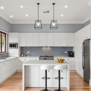 This is an example of a mid-sized transitional u-shaped open plan kitchen in Sydney with an undermount sink, shaker cabinets, white cabinets, quartz benchtops, grey splashback, ceramic splashback, stainless steel appliances, light hardwood floors, with island, brown floor and grey benchtop.