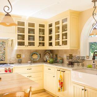 他の地域の中サイズのシャビーシック調のおしゃれなキッチン (アンダーカウンターシンク、落し込みパネル扉のキャビネット、黄色いキャビネット、ベージュキッチンパネル、セラミックタイルのキッチンパネル、シルバーの調理設備の、淡色無垢フローリング) の写真