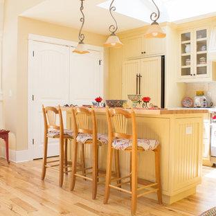 他の地域の中サイズのシャビーシック調のおしゃれなキッチン (アンダーカウンターシンク、落し込みパネル扉のキャビネット、黄色いキャビネット、ベージュキッチンパネル、石タイルのキッチンパネル、シルバーの調理設備の、淡色無垢フローリング) の写真