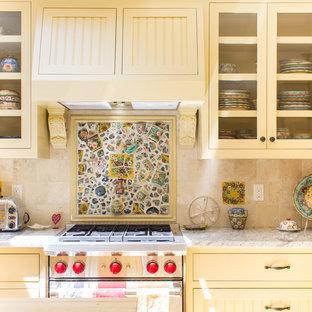 他の地域の中サイズのシャビーシック調のおしゃれなキッチン (アンダーカウンターシンク、落し込みパネル扉のキャビネット、黄色いキャビネット、ベージュキッチンパネル、モザイクタイルのキッチンパネル、シルバーの調理設備の、淡色無垢フローリング) の写真