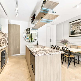 Inspiration for a small contemporary galley open plan kitchen in Sydney with an undermount sink, light wood cabinets, marble benchtops, multi-coloured splashback, marble splashback, black appliances, light hardwood floors, with island, beige floor, flat-panel cabinets and multi-coloured benchtop.