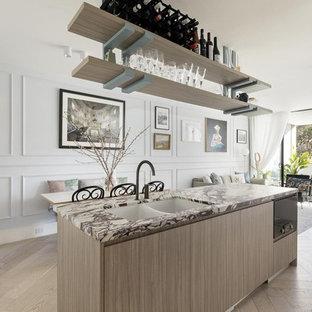 Modern inredning av ett litet lila lila kök, med en undermonterad diskho, skåp i ljust trä, marmorbänkskiva, flerfärgad stänkskydd, stänkskydd i marmor, svarta vitvaror, ljust trägolv, en köksö och beiget golv