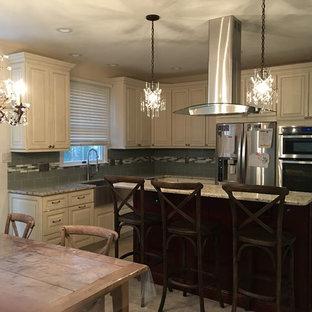 Idéer för mellanstora vintage kök, med en rustik diskho, luckor med upphöjd panel, vita skåp, granitbänkskiva, grönt stänkskydd, stänkskydd i glaskakel, rostfria vitvaror, linoleumgolv och en köksö