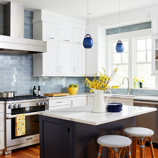 Inspiration for a medium sized classic u-shaped kitchen/diner in DC Metro with a submerged sink, recessed-panel cabinets, white cabinets, engineered stone countertops, brown splashback, glass tiled splashback, stainless steel appliances, medium hardwood flooring and an island.