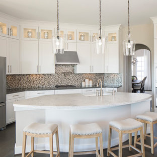 Transitional kitchen designs - Kitchen - transitional l-shaped brown floor kitchen idea in Austin with a farmhouse sink, shaker cabinets, white cabinets, mosaic tile backsplash, stainless steel appliances and an island