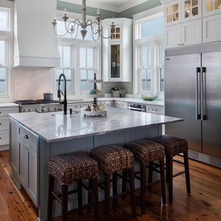 Example of a coastal medium tone wood floor and brown floor kitchen design in New Orleans with a farmhouse sink, shaker cabinets, white cabinets, stainless steel appliances, an island and white countertops