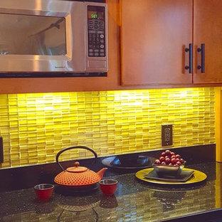 他の地域の中サイズのアジアンスタイルのおしゃれなキッチン (フラットパネル扉のキャビネット、中間色木目調キャビネット、御影石カウンター、ガラス板のキッチンパネル) の写真
