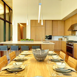 Contemporary eat-in kitchen remodeling - Example of a trendy l-shaped brown floor eat-in kitchen design in Other with an undermount sink, flat-panel cabinets, brown cabinets, white backsplash, stainless steel appliances and a peninsula
