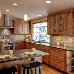 シアトルの中サイズのアジアンスタイルのおしゃれなキッチン (アンダーカウンターシンク、シェーカースタイル扉のキャビネット、中間色木目調キャビネット、人工大理石カウンター、グレーのキッチンパネル、ボーダータイルのキッチンパネル、シルバーの調理設備の、淡色無垢フローリング、ベージュの床) の写真