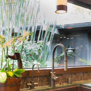 Foto på ett mellanstort orientaliskt l-kök, med en undermonterad diskho, släta luckor, skåp i mellenmörkt trä, bänkskiva i kvartsit, brunt stänkskydd, stänkskydd i keramik, integrerade vitvaror, mellanmörkt trägolv och en köksö