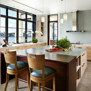 Стильный дизайн: большая угловая кухня в восточном стиле с врезной раковиной, плоскими фасадами, светлыми деревянными фасадами, техникой из нержавеющей стали, бетонным полом, островом, обеденным столом, столешницей из гранита, синим фартуком, фартуком из плитки кабанчик и коричневым полом - последний тренд