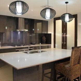 シドニーの中サイズのアジアンスタイルのおしゃれなキッチン (ドロップインシンク、フラットパネル扉のキャビネット、グレーのキャビネット、グレーのキッチンパネル、ガラス板のキッチンパネル、シルバーの調理設備、磁器タイルの床、御影石カウンター) の写真