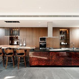 Foto de cocina de galera, de estilo zen, con fregadero encastrado, armarios con paneles lisos, puertas de armario de madera oscura, electrodomésticos de acero inoxidable, una isla, suelo gris y encimeras negras