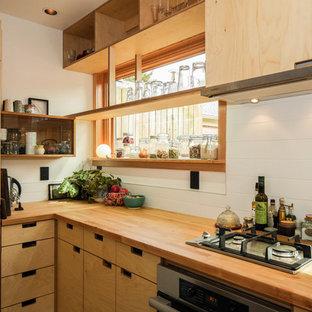 Diseño de cocina de estilo zen con armarios con paneles lisos, puertas de armario de madera clara, encimera de madera, salpicadero blanco y salpicadero de azulejos de cerámica