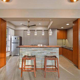 Modelo de cocina en L, asiática, pequeña, abierta, con fregadero bajoencimera, armarios con paneles lisos, puertas de armario de madera oscura, salpicadero beige, electrodomésticos de acero inoxidable, una isla y suelo beige
