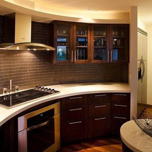 ハワイの中サイズのアジアンスタイルのおしゃれなアイランドキッチン (濃色木目調キャビネット、人工大理石カウンター、茶色いキッチンパネル、ボーダータイルのキッチンパネル、シルバーの調理設備の、濃色無垢フローリング、茶色い床) の写真