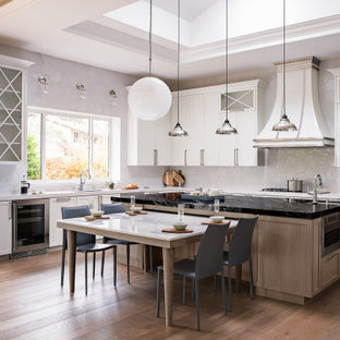 Design ideas for a large transitional l-shaped eat-in kitchen in San Francisco with shaker cabinets, white cabinets, white splashback, ceramic splashback, stainless steel appliances, medium hardwood floors, with island, brown floor, an undermount sink, white benchtop and recessed.