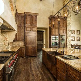 Exempel på ett mycket stort klassiskt kök, med en köksö, luckor med upphöjd panel, skåp i mörkt trä, granitbänkskiva, beige stänkskydd, stänkskydd i terrakottakakel, rostfria vitvaror, en rustik diskho och mörkt trägolv
