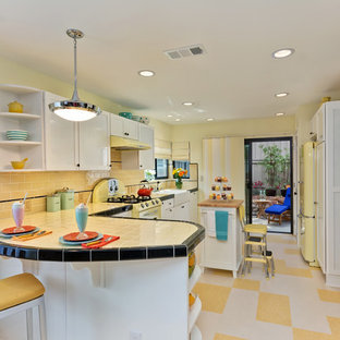На фото: со средним бюджетом угловые кухни среднего размера в классическом стиле с раковиной в стиле кантри, фасадами в стиле шейкер, белыми фасадами, столешницей из плитки, желтым фартуком, фартуком из плитки кабанчик, цветной техникой, полом из линолеума, островом, разноцветным полом и желтой столешницей