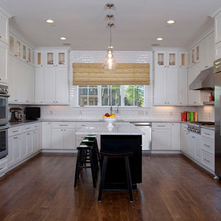 Mid-sized transitional l-shaped dark wood floor and brown floor eat-in kitchen photo in Columbus with an undermount sink, shaker cabinets, white cabinets, marble countertops, white backsplash, subway tile backsplash, stainless steel appliances and an island