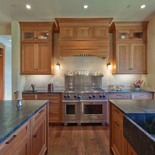 This is an example of a traditional kitchen in Denver with an integrated sink, shaker cabinets, medium wood cabinets, beige splashback, stainless steel appliances and green benchtop.