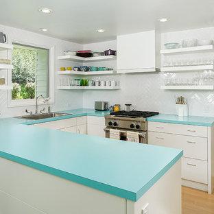 Inredning av ett klassiskt litet turkos turkost u-kök, med en nedsänkt diskho, släta luckor, vita skåp, laminatbänkskiva, vitt stänkskydd, stänkskydd i tunnelbanekakel, rostfria vitvaror, mellanmörkt trägolv och en halv köksö