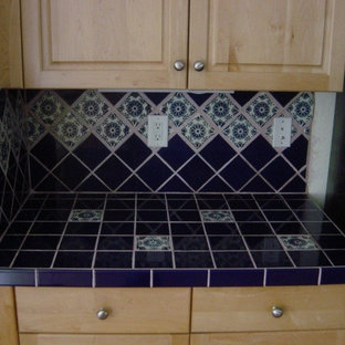 マイアミの中サイズの地中海スタイルのおしゃれなダイニングキッチン (アンダーカウンターシンク、レイズドパネル扉のキャビネット、淡色木目調キャビネット、タイルカウンター、青いキッチンパネル、セラミックタイルのキッチンパネル、シルバーの調理設備の、テラコッタタイルの床、アイランドなし) の写真