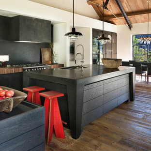 Rustic eat-in kitchen ideas - Eat-in kitchen - rustic galley medium tone wood floor and brown floor eat-in kitchen idea in Other with an undermount sink, flat-panel cabinets, black cabinets, black backsplash, an island and black countertops