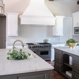 Transitional kitchen in Dallas with raised-panel cabinets, white cabinets, white splashback, stainless steel appliances, brick floors, multiple islands and white benchtop.