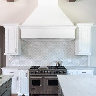 Inredning av ett klassiskt vit vitt kök, med luckor med upphöjd panel, vita skåp, vitt stänkskydd, rostfria vitvaror, tegelgolv och flera köksöar