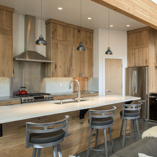 Rustic open concept kitchen designs - Open concept kitchen - rustic concrete floor and gray floor open concept kitchen idea in Boise with an undermount sink, flat-panel cabinets, light wood cabinets, metallic backsplash, stainless steel appliances, an island and white countertops
