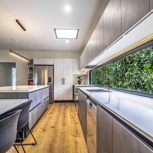 Inspiration for a contemporary u-shaped kitchen in Melbourne with a double-bowl sink, flat-panel cabinets, grey cabinets, stainless steel appliances, medium hardwood floors and brown floor.
