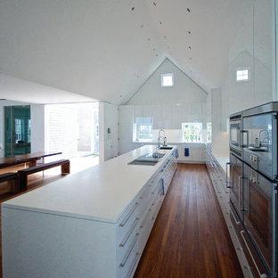Diseño de cocina en U, de estilo de casa de campo, extra grande, abierta, con fregadero bajoencimera, armarios con paneles lisos, puertas de armario blancas, encimera de acrílico, salpicadero blanco, salpicadero de vidrio templado y electrodomésticos de acero inoxidable