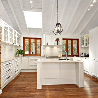 Mid-sized transitional u-shaped kitchen in Sydney with a drop-in sink, raised-panel cabinets, white cabinets, white splashback, stainless steel appliances, medium hardwood floors, multiple islands and brown floor.