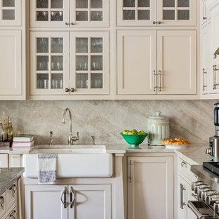 ボストンのトラディショナルスタイルのおしゃれなキッチン (エプロンフロントシンク、シェーカースタイル扉のキャビネット、ベージュのキャビネット、ベージュキッチンパネル、石スラブのキッチンパネル、白い調理設備、ベージュのキッチンカウンター) の写真