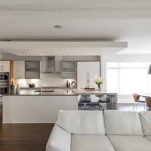 Immagine di una cucina design con ante lisce, ante bianche, paraspruzzi bianco, elettrodomestici in acciaio inossidabile e paraspruzzi con lastra di vetro