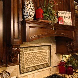 Diseño de cocina de galera, clásica, grande, abierta, con armarios con paneles con relieve, puertas de armario de madera oscura, encimera de granito, salpicadero beige, salpicadero de azulejos de piedra, electrodomésticos de acero inoxidable, suelo de terrazo y una isla