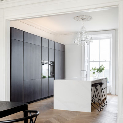 Kitchen - contemporary galley medium tone wood floor and brown floor kitchen idea in Dublin with an undermount sink, flat-panel cabinets, dark wood cabinets, an island and white countertops